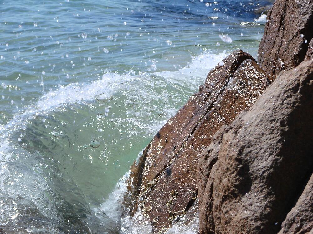 water splashing onto rocks by fontmedia