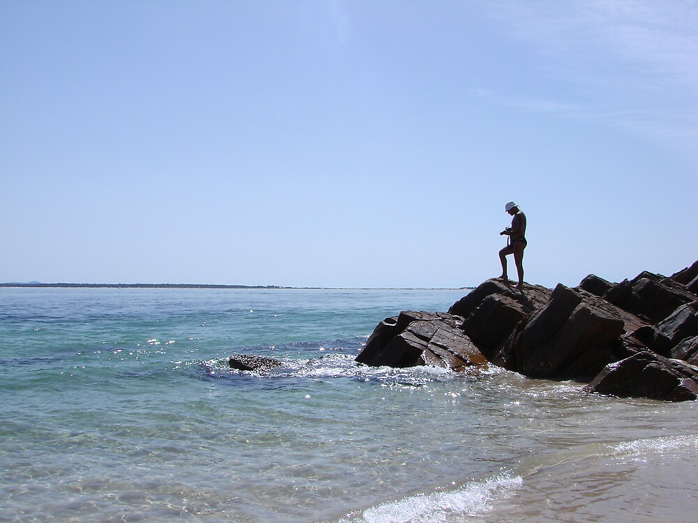 photogrpaher on a rock at the beach by fontmedia