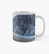snowy road through mountains in evening Mug
