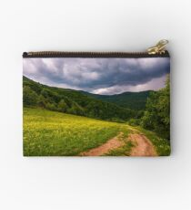 grassy field on hillside in stormy weather Studio Pouch