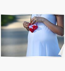 A pregnant woman holding baby shoes Poster