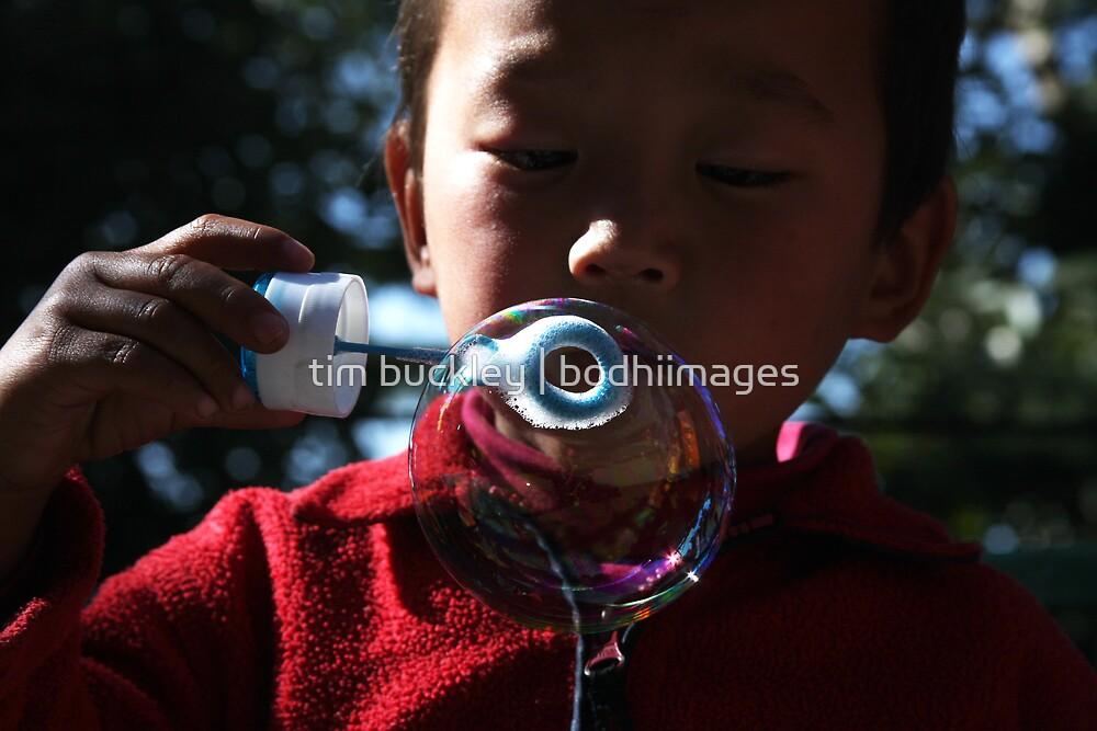 bubble. young tibetan boy, india by tim buckley   bodhiimages