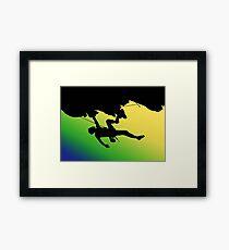 Silhouette man climbing mountain Framed Print