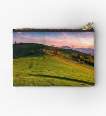grassy pasture on hillside at sunset Studio Pouch
