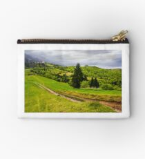 dirt road through grassy slope in rural area Studio Pouch