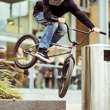 A bmx rider doing a trick through a tight gap by clemphoto