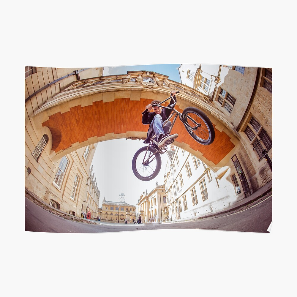 A BMX rider does a jump underneath an arch in Oxford Poster