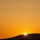 Gold orb sun slips below mountain silhouette by Rod Raglin