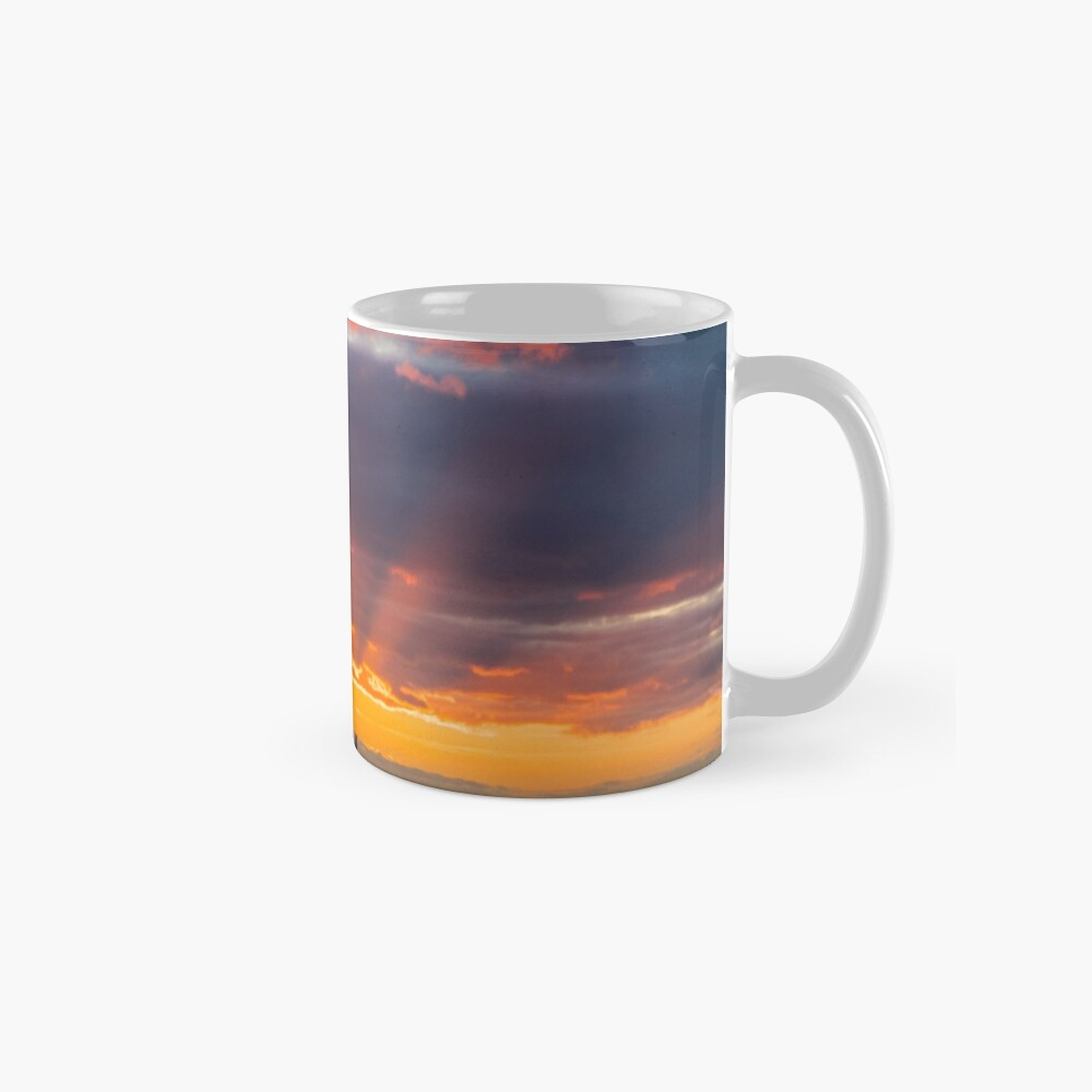 Red starburst sunset behind rocks and lighthouse Mugs