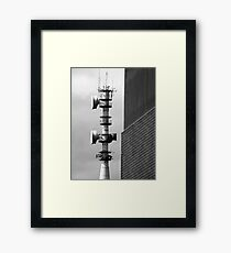 Communications tower bristling with antennas and aerials with contrasting walls and moody sky Framed Print