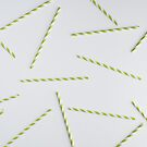 Colorful green paper straws on white background by Adam Nixon