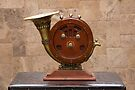 Antique round wood AM/FM radio with brass horn ornate speaker on pedestal on table by Kendall Anderson