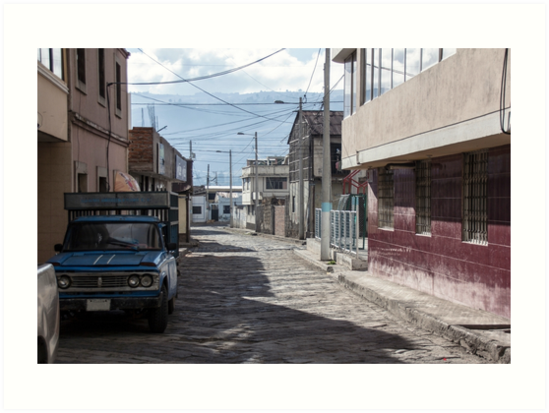 Empty quiet winding cobblestone street in Guamote, Ecuador with blue truck, red tile building, power lines and street lamps by Kendall Anderson