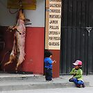 Kids playing in front of butcher shop, Alausi, Ecuador by Kendall Anderson