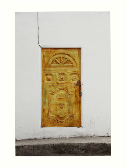 Golden yellow door in white wall by Kendall Anderson