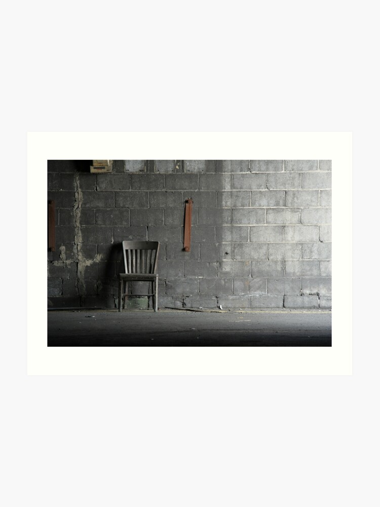 Abandoned Wooden Grey Chair Resting Against A Grey Concrete Block Wall In An Abandoned Carbide Graphite Industrial Factory Art Print