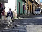 Man wearing purple poncho rides donkey up cobblestone street in Guamote, Ecuador by Kendall Anderson