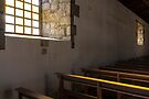 Soft light from window well on to church pews, through stone block wall, Colta, Ecuador by Kendall Anderson