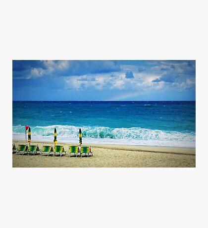 Deck chairs on beach with faraway rainbow Photographic Print