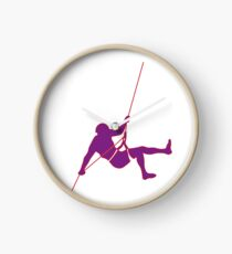 Climber climbing on the wall hill in purple Clock