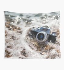 Retro photo camera in the water on the beach, sinks in sea foam Wall Tapestry