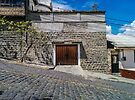 Steep cobblestone street with block house garage, Quito, Ecuador by Kendall Anderson