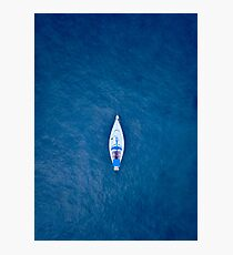 A drone shot of a sailing boat surrounded by deep blue sea water Photographic Print