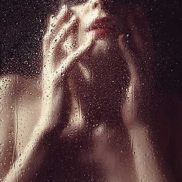 Beautiful woman photographed behind a window with rain drops by artfx