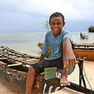 Kiriwina kid with outrigger canoe by styles