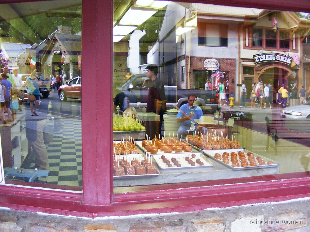 Man eating candy apple reflected in candy apple shop by raindancerwoman