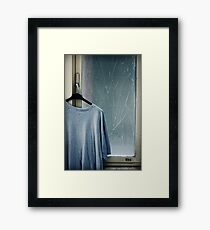 Hanging T-shirt and broken window pane Framed Print