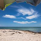 View of the beach from under an umbrella by Adam Nixon