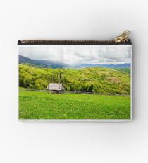 woodshed on grassy hill in rural area Studio Pouch
