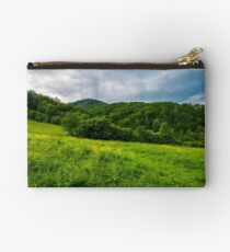 grassy pasture near the forest in stormy weather Studio Pouch