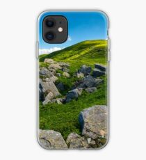 huge rocky formation on the grassy hillside iPhone Case