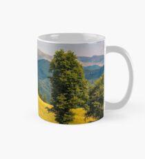 tree on the grassy hillside Mug