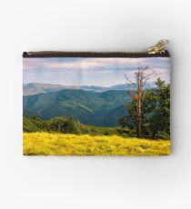 trees on a hillside with mountains in the distance Studio Pouch