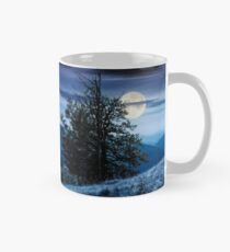 tree on the grassy hillside on at night Mug