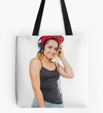 Playful female teen with headphones and red baseball cap wearing black top  Tote Bag