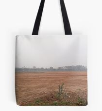 A wide open dusty field surrounded by cars, trees and buildings Tote Bag