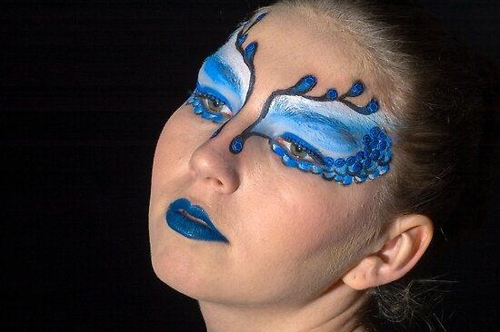 young teenage female model with blue and white elaborate make up mask on black background by PhotoStock-Isra