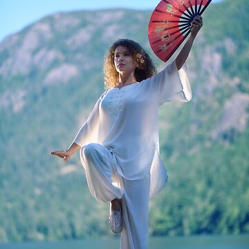 Woman practicing Tai Chi crane stance with a fan at the mountain lake shore in the morning art photo print by AwenArtPrints