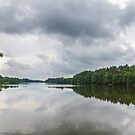 Cloudy sky over calm lake by Lukasz Szczepanski