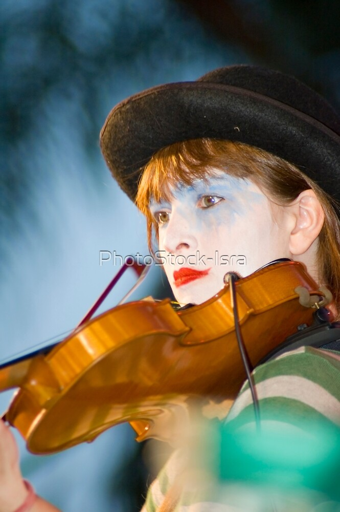 Musician dressed and made up as a clown playing a violin on stage by PhotoStock-Isra