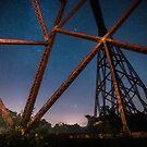 A rusty railroad Trestle illuminated late at night  by Sam Noble