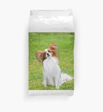 Portrait of a papillon purebreed dog sitting on the grass Duvet Cover