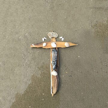 Driftwood cross on beach sand by sdawsoncc