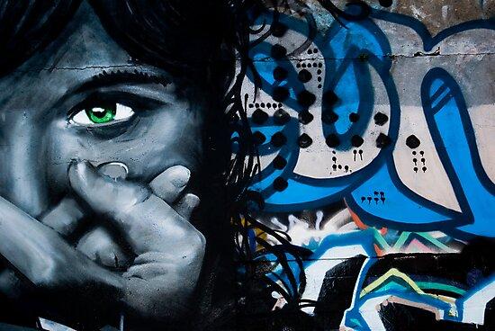 Graffiti face on the textured brick wall by yurix