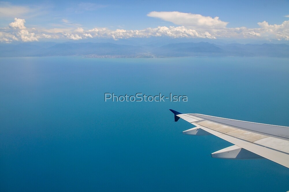 Elevated view of the Mediterranean Sea and clouds as seen through the window of an Airbus A320-200 plane  by PhotoStock-Isra