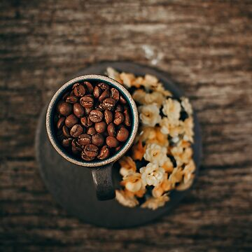 Birds eye view of coffee beansin a mug with popcorn on the side by franceslewis